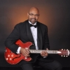 Formal photo of Doug Martin with guitar.